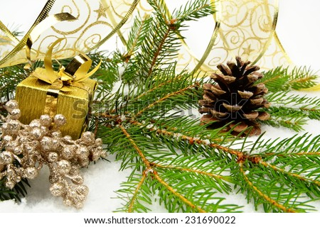 Decoration of golden christmas gifts, golden ribbon on snow christmas tree branch on white - stock photo