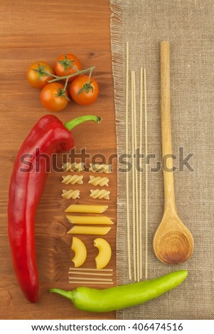 Decoration of pasta. Preparing homemade food. Different kinds of pasta on the wooden background. Creating the menu. Place for your text. - stock photo