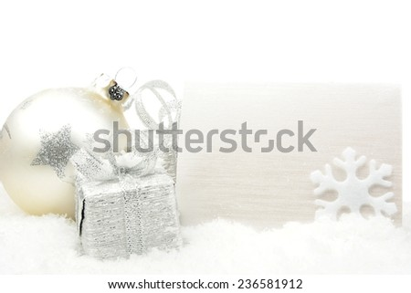 Decoration of silver christmas baubles and gifts with wishes card on snow white background - stock photo