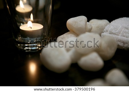 Decoration of spa procedures; burning candle with white stones