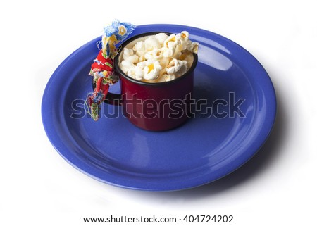 Decoration of traditional Brazilian Festa Junina Party, cute red cup decorated with popcorn over a blue plate on white background..