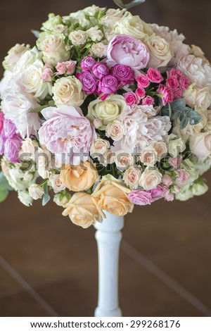 Decoration of wedding nosegay of fresh beautiful flowers of roses and peony white pink violet purple yellow lilac and orange colours in slim vase indoor, vertical picture - stock photo