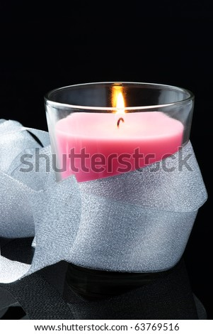 Decoration with pink burning candle and shining silver ribbon on black - stock photo