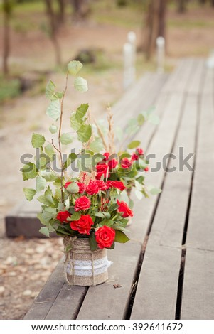 Decorations in rustic style: beautiful bouquets from red roses in a flowerspot decorated by sackcloth
