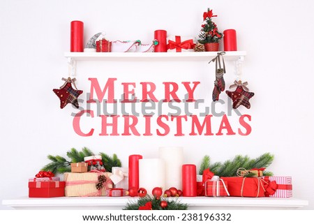 Decorations with Merry Christmas inscription on mantelpiece on white wall background - stock photo