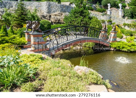 Decorative arched bridge over a pond with statues of griffins among the vegetation of the park