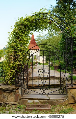 Decorative arched iron gateway to a garden - stock photo