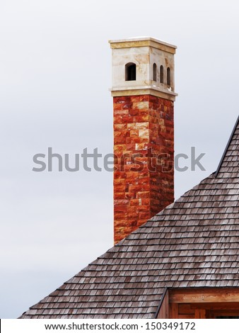 decorative artistic chimney on building a new roof of home  - stock photo