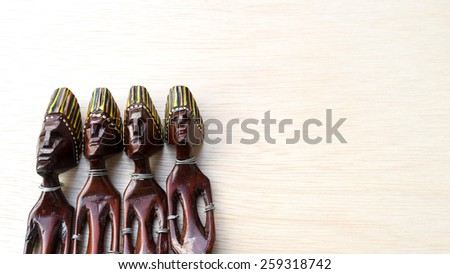 Decorative Asian or African tribal totem carved from forest wood on clean wooden surface. Concept of family member and aboriginal art. Slightly defocused and close-up shot. Copy space.