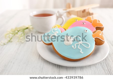 Decorative baby cookies with cup of  tea on plate - stock photo