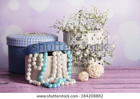 Decorative boxes with beads and flowers on table on bright background - stock photo