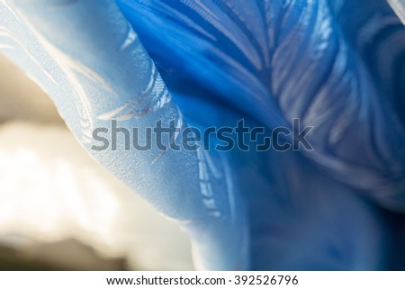 Decorative bright blue curtain against window macro background.
