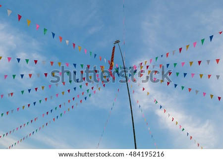 Decorative bright colorful triangle festive flags with blue sky and tall bamboo pole background