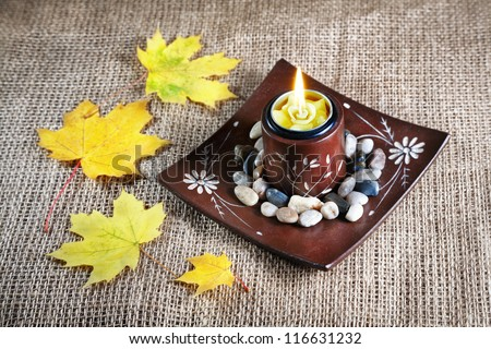 Decorative brown candle holder with stones and yellow maple leaves on textured background - stock photo