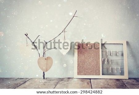 decorative bulletin board with ropes and wooden clothespins and hanging hearts over wooden table. ready for text or mockup. retro filtered image with glitter overlay  - stock photo