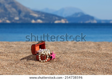 Decorative chest with jewelry and starfish on a beach - stock photo