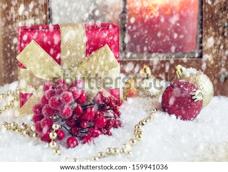 Decorative christmas composition. Postcard. Gift box, balls, berries in snow. Selective focus.