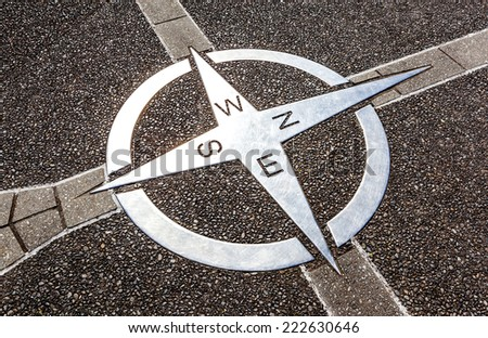 Decorative compass on the cement ground, for getting direction - stock photo