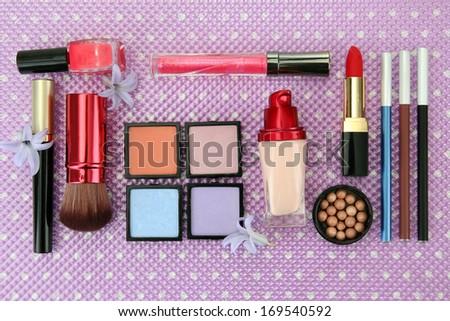 Decorative cosmetics on purple background - stock photo