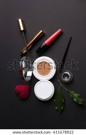 Decorative cosmetics with orchid flower with wool heart shape on black background
