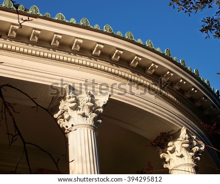 Decorative cresting, dentils, Corinthian columns and more adorn the roof line and facade of a curved porch on a beautiful old Victorian era home.  - stock photo