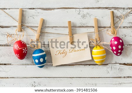Decorative easter eggs hanging on thin rope, card with wishes in portuguese, light planks in the background/Have a peaceful easter!/Happy Easter - stock photo