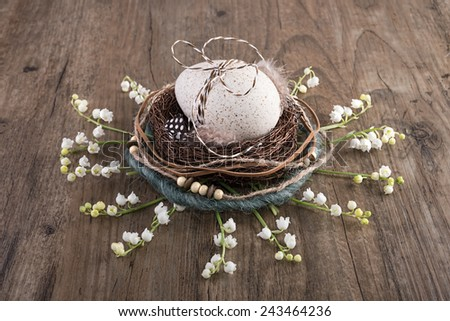 Decorative Easter nest on oak table with duck egg and lily of the valley flowers - stock photo
