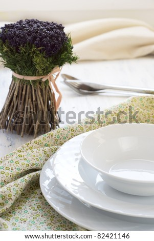 decorative flowers and plates on a table - stock photo