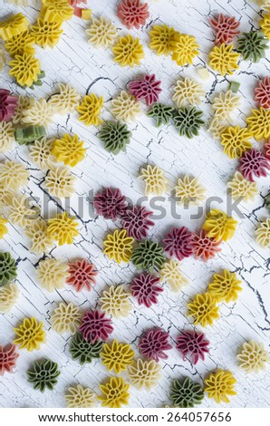 Decorative frame of five color flower pasta on white cracked background as texture or background - stock photo