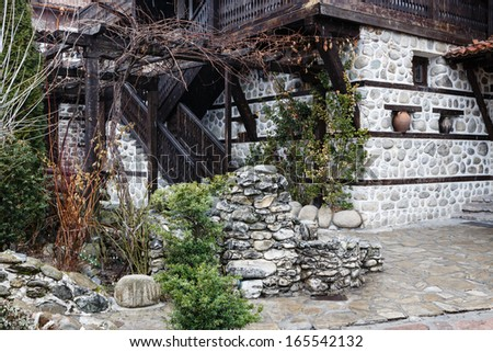 Decorative garden in the yard of the ancient house - stock photo
