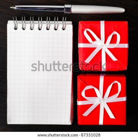 decorative gift boxes with notepad on dark table - stock photo