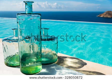 decorative glass bottles in front of a pool at the seasids - stock photo