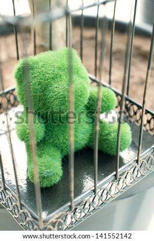 Decorative green bear in a cage, vertical shot