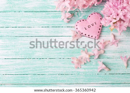 Decorative heart  and  hyacinths flowers  on turquoise painted wooden planks. Selective focus. Place for text. - stock photo