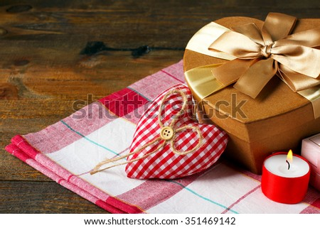Decorative heart for Valentine's day with candle and gift on fabric on wooden background