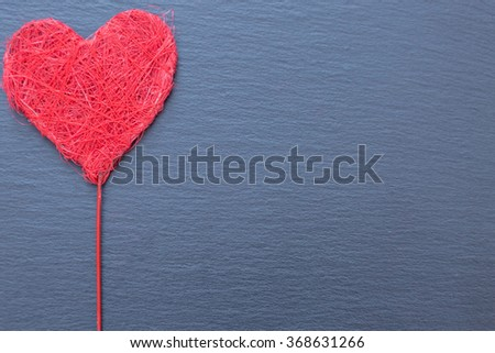 Decorative heart made of yarn on stick. Grey ribbed background, copy space - stock photo