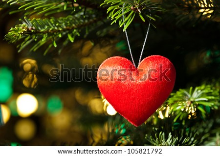 Decorative heart shape ornament in a Christmas tree A - stock photo