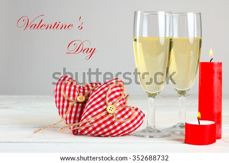 decorative hearts and champagne glasses with candles on wooden table