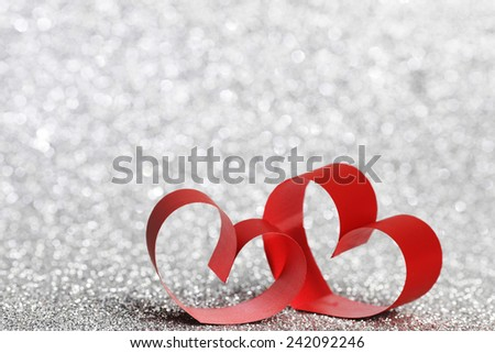 Decorative hearts of red ribbon on shiny glitter background - stock photo