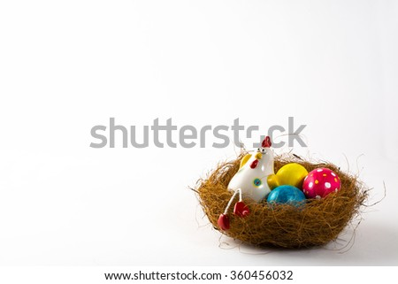 Decorative Hen in a nest with painted Easter eggs on a white background. Easter background. Easter background. Easter symbol. Copy space - stock photo