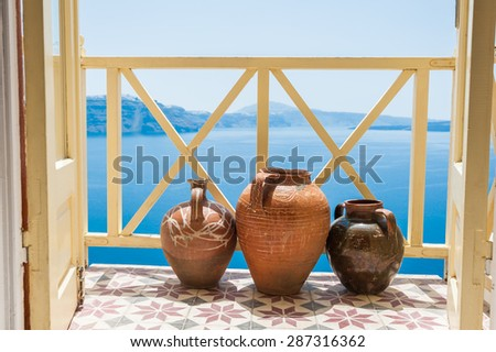 Decorative jugs on the balcony. Beautiful landscape with sea view. Santorini island, Greece.  - stock photo