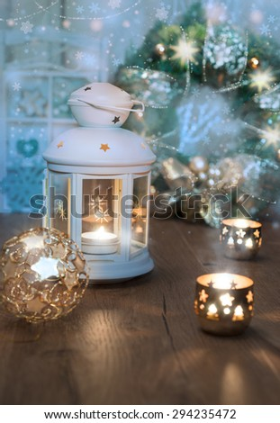 Decorative lantern, candles and Christmas decorations on vintage kitchen. Shallow DOF, focus on the lantern glass  - stock photo