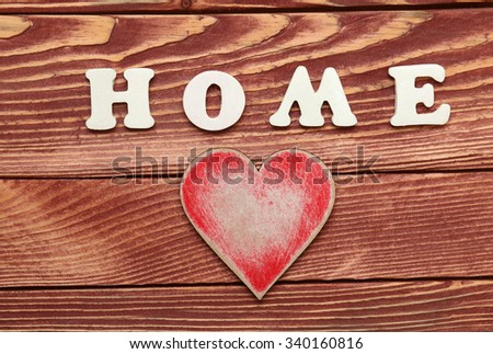Decorative letters forming word HOME with vintage heart on wooden background - stock photo