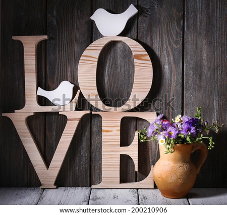 Decorative letters forming word LOVE with wildflowers on wooden background - stock photo