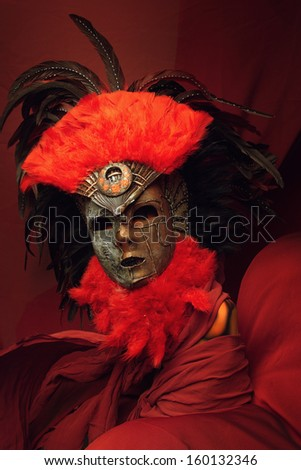 Decorative mask with red and black feathers on a red background