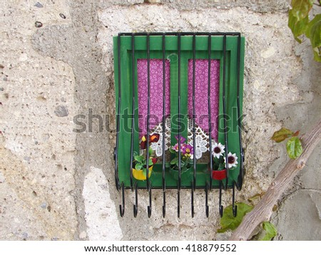 Decorative miniature window frame with metallic bars, curtains and flower pots - stock photo