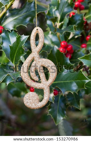 Decorative music note hanging on holly sprigs (manual focus) - stock photo