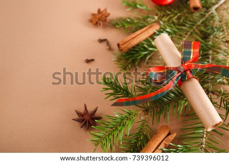 Decorative old paper scroll tied up with satin ribbon bow on pine branch with cinnamon at beige background with copy cpace. Winter or any holiday concept