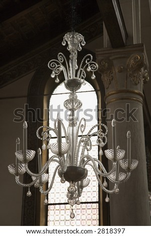Decorative ornate crystal chandelier hanging from ceiling.