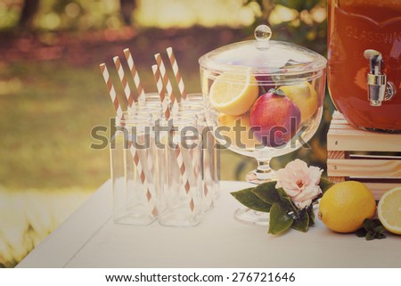 Decorative outdoor party drink station with small bottles and homemade peach lemonade - stock photo